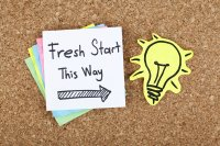 "Bulletin board with sticky note that reads ""Fresh start this way"""