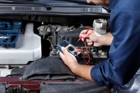 Automotive technician diagnosing engine trouble