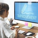 """Woman in front of computer with """"improvement"""" written on the screen"""